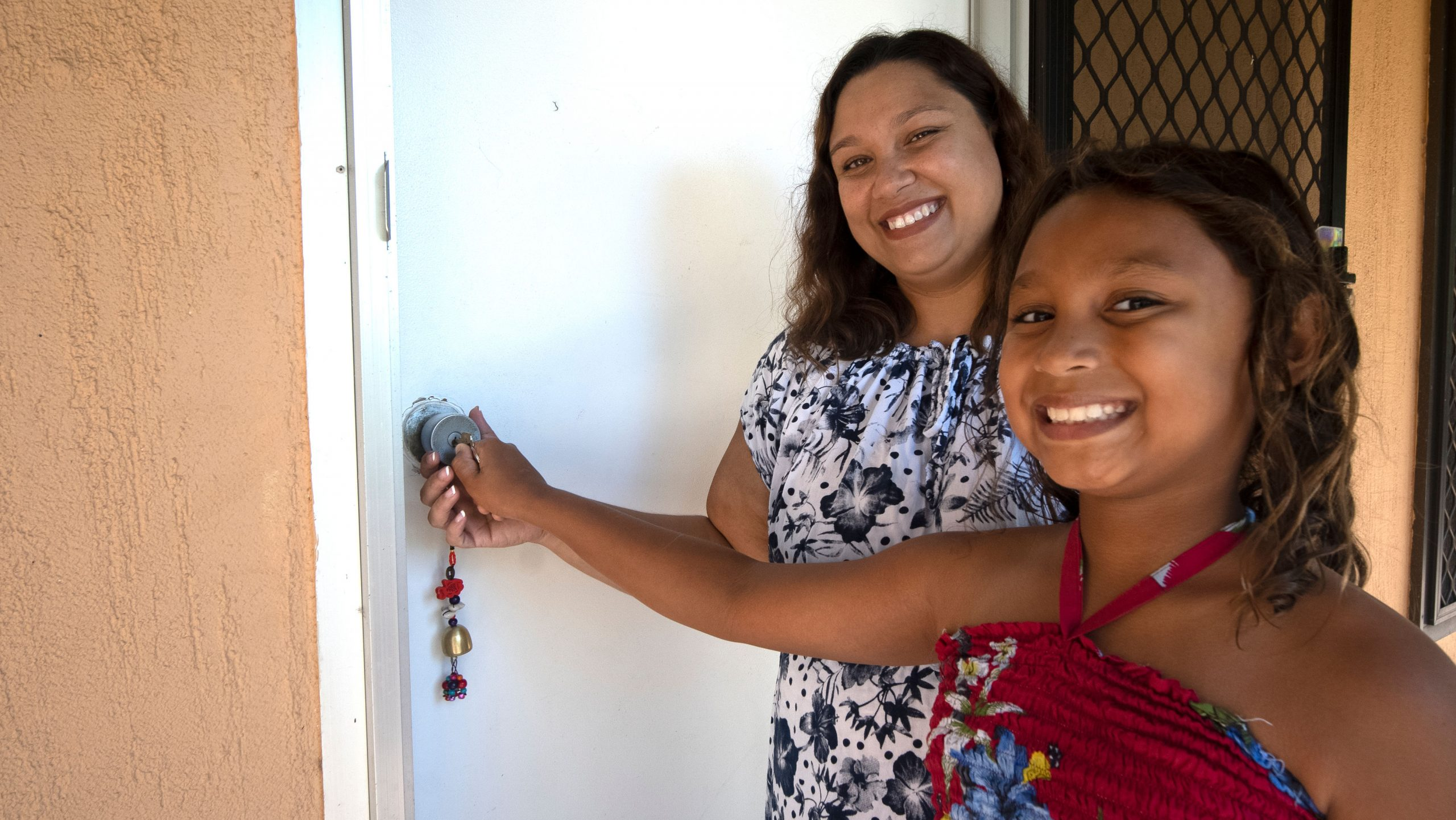 Photo of mother and daughter opening the door to their new home