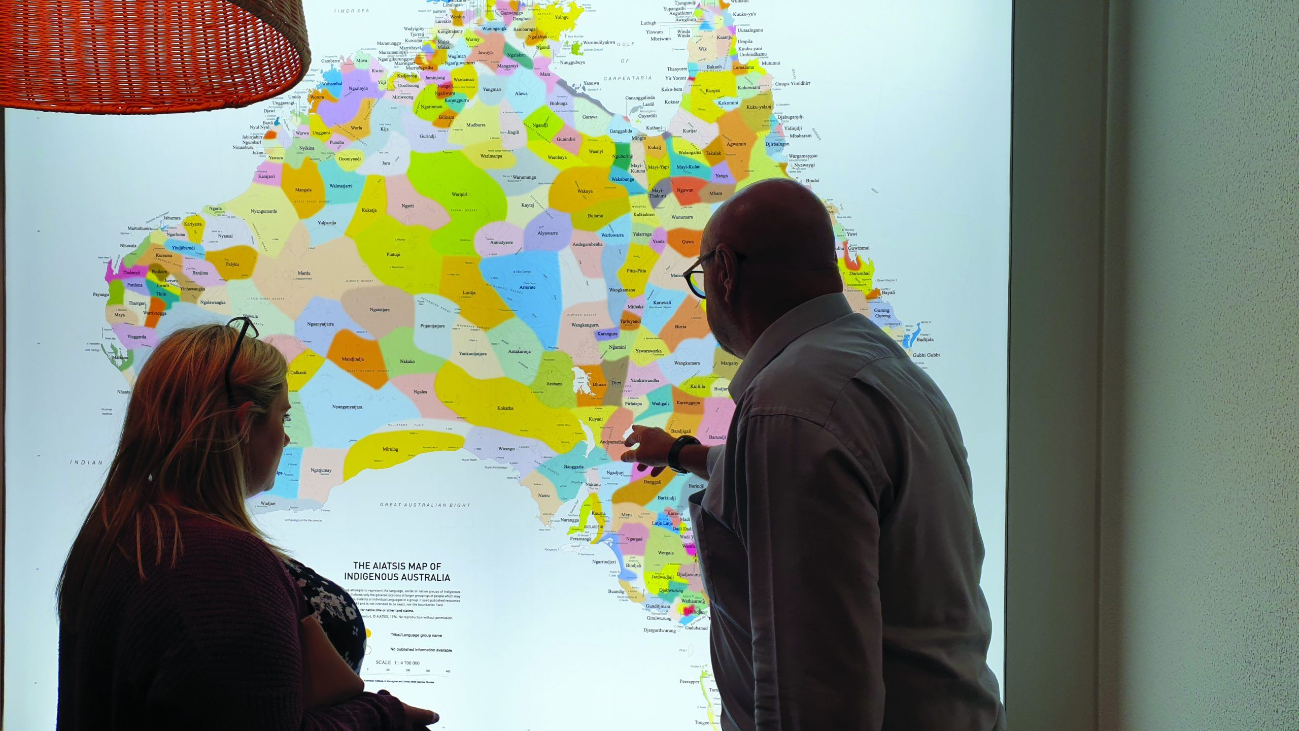 Image of IBA staff reviewing the map of Indigenous Australia in the foyer of our Brisbane office